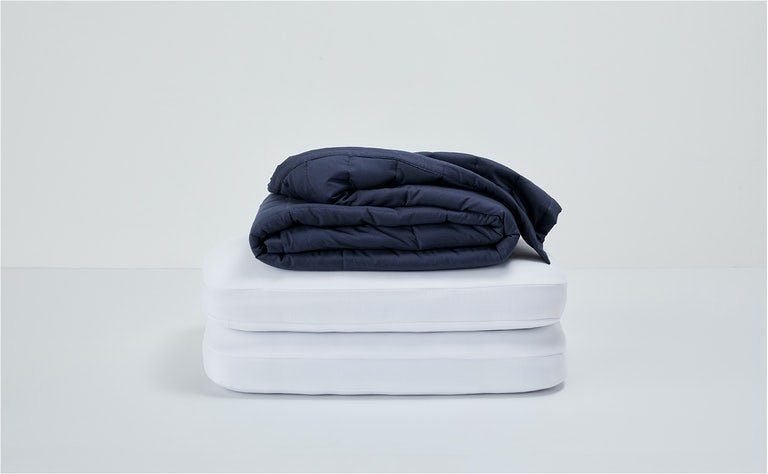 Folded weighted blanket stacked on top of 2 foam pillows