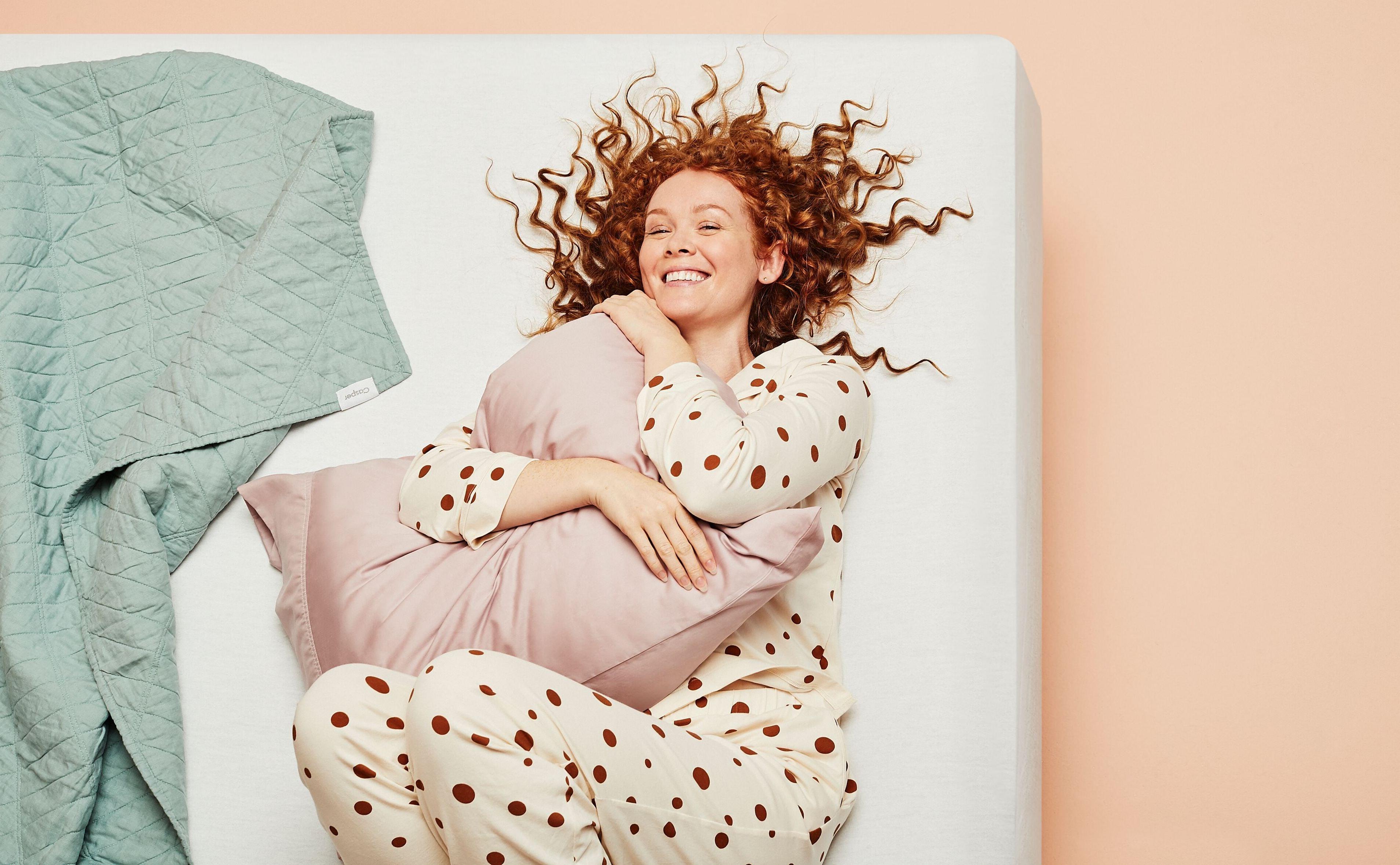 Girl hugging pillow and laughing on her Casper mattress