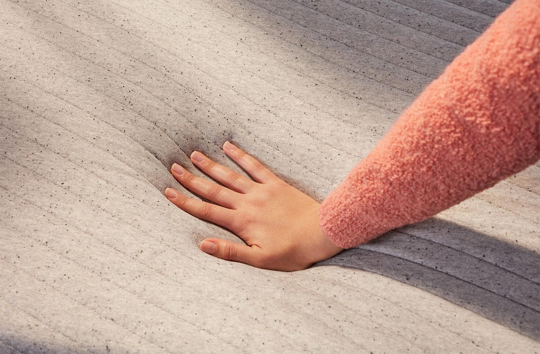 Hand pressing on Casper Nova Foam mattress