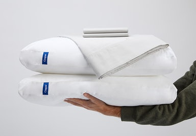 Sheet set stacked on top of 2 pillows