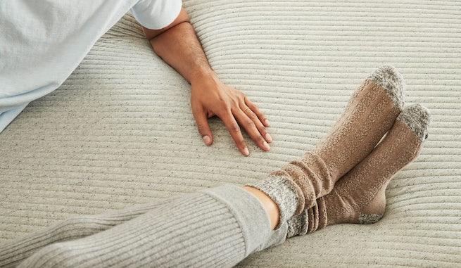 Feet and hand pressing on Original foam mattress