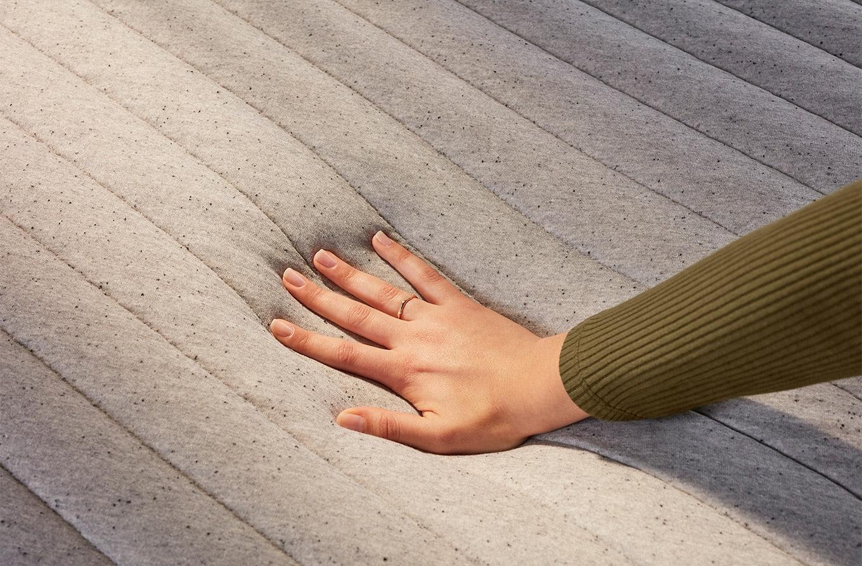 Hand touching Casper Wave mattress
