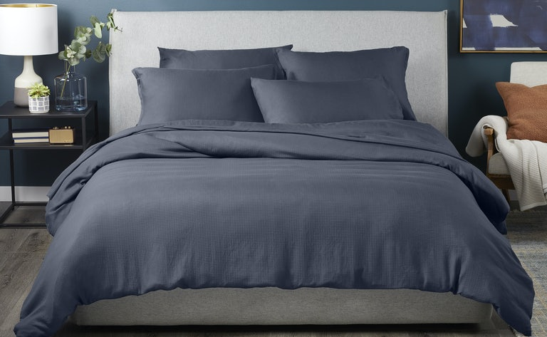 Woman putting hyperlite sheets on the bed