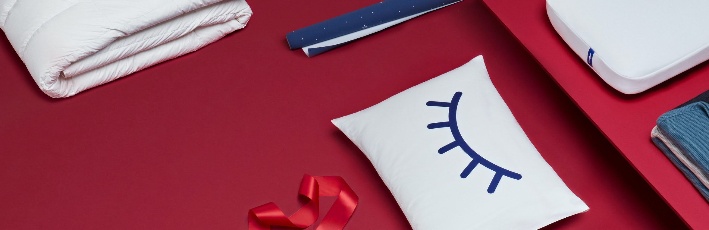 Flat lay of Casper pillows and duvet on a red background