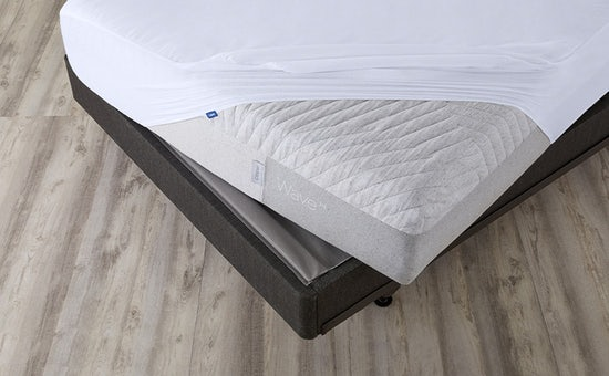 Corner of Wave Hybrid mattress covered by a mattress protector on a foundation and metal bed frame