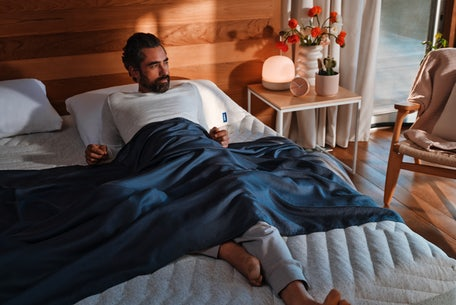 Man lounges comfortably on a Wave Hybrid Snow mattress bed while covered with a Hyperlite sheet.