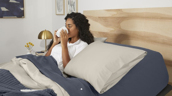Woman drinking from mug in bed