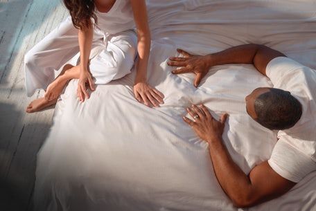A couple relaxing in bed, runs their fingers through Hyperlite sheets.