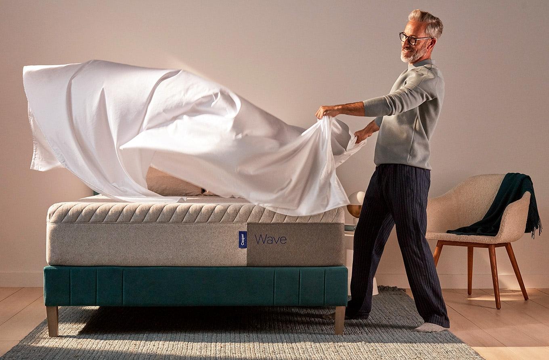 Man putting sheets on a Casper Wave mattress
