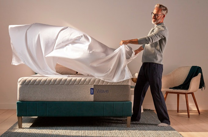 Man putting sheets on a Casper Wave mattress